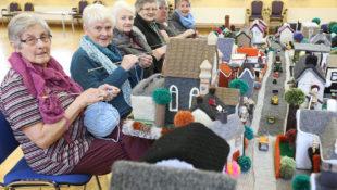 Diese Damen haben ein Modell ihres Dorfes mit Häkelarbeit nachgebaut